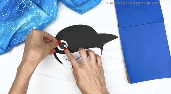 hand gluing eye to killer whale paper bag craft
