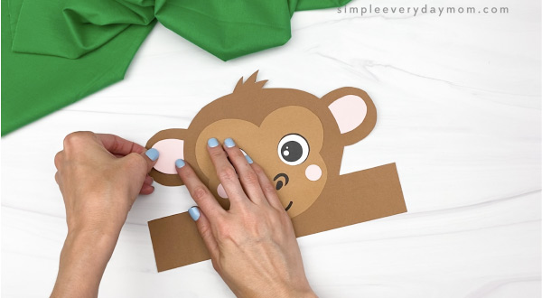 hand gluing inner ear to monkey headband craft