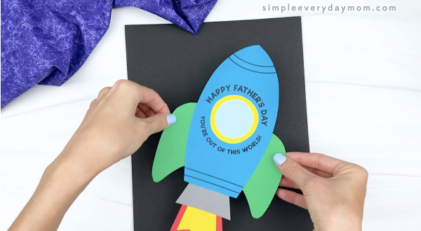 hand gluing rocket to black paper