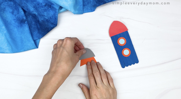 hand gluing flame to engine of popsicle stick rocket