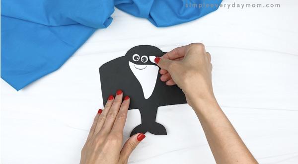hand gluing eye spot onto toilet paper roll killer whale craft