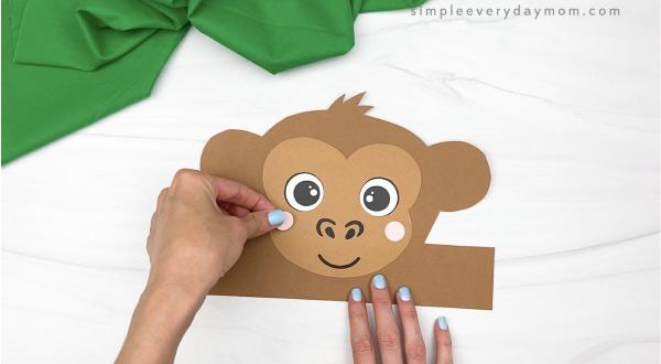 hand gluing cheek to monkey headband craft