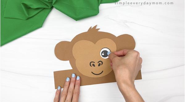 hand gluing eye to monkey headband craft