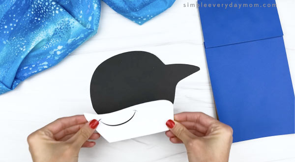 hand gluing mouth to killer whale paper bag craft