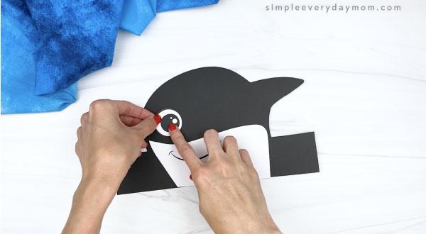 hand gluing eye to killer whale headband craft