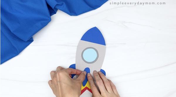 hand gluing fin to rocket headband craft