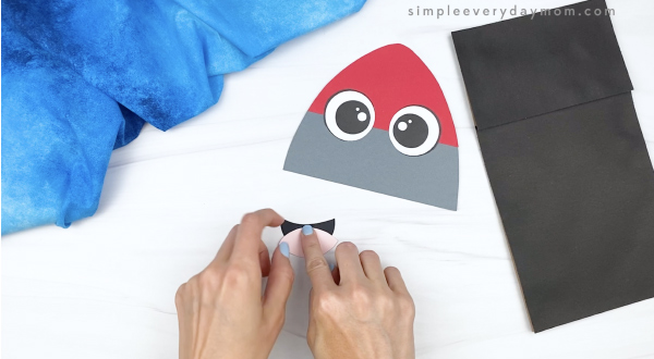 hand gluing tongue to mouth of rocket puppet craft