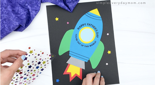 hand placing star stickers on rocket father's day card
