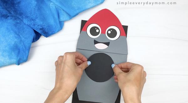 hand gluing window frame to rocket puppet