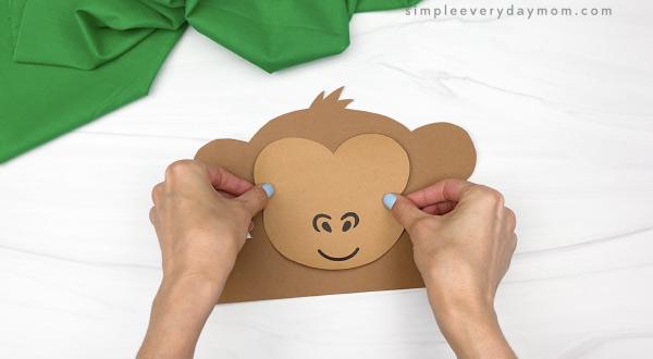 hand gluing face to monkey headband craft