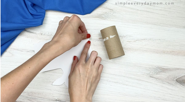 hand placing tape on paper roll beluga craft