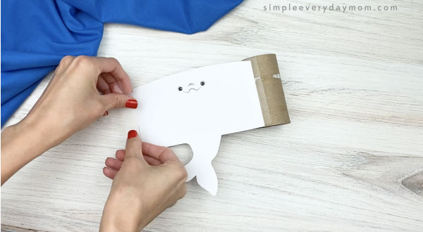 hand taping beluga template onto toilet paper roll