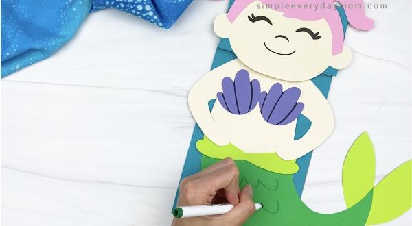 hand drawing scales on paper bag mermaid