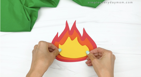 hand gluing yellow flame to paper campfire craft
