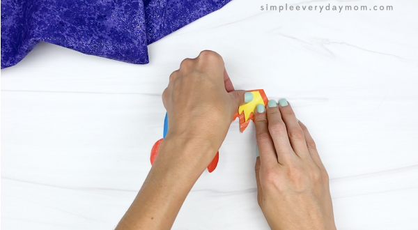 hand gluing inner flame to outer flame of cut and paste rocket craft