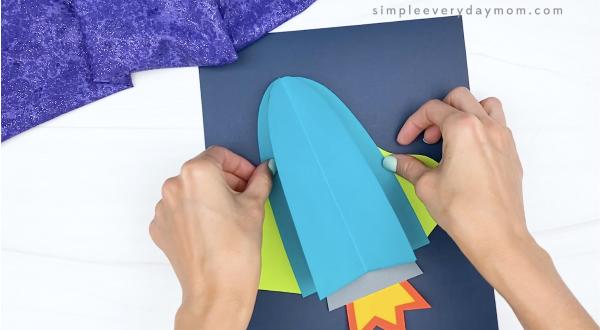 hand gluing 3d rocket onto dark blue paper