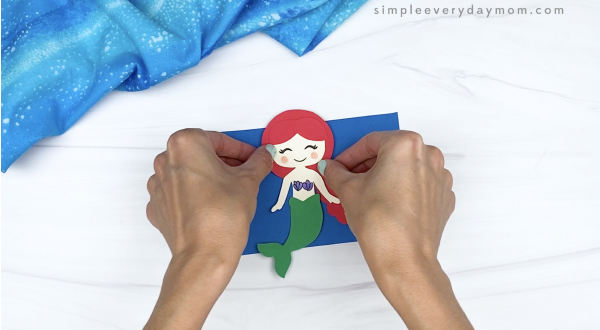 hand gluing mermaid to blue rectangle