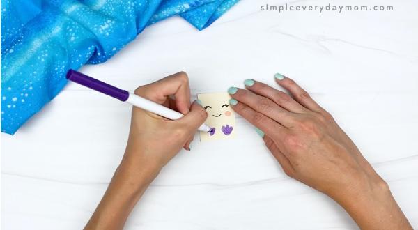 hand drawing mermaid top onto popsicle stick mermaid