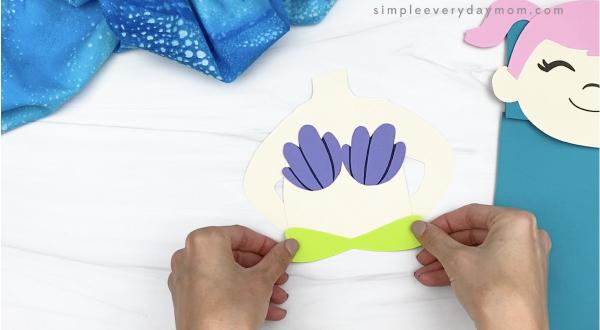 hand gluing top of mermaid tail to torso of paper bag mermaid