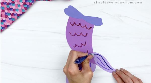 hand using glitter glue on mermaid tail craft