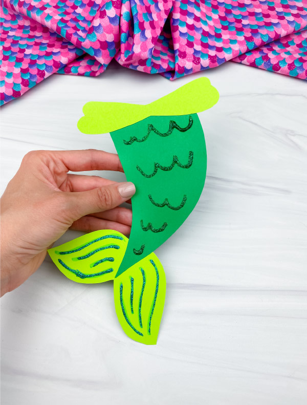 hand holding green mermaid tail craft
