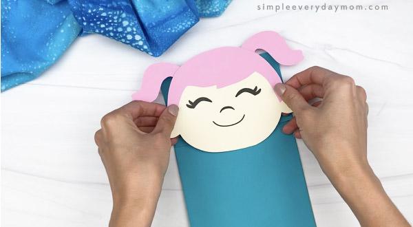 hand gluing head to paper bag mermaid craft