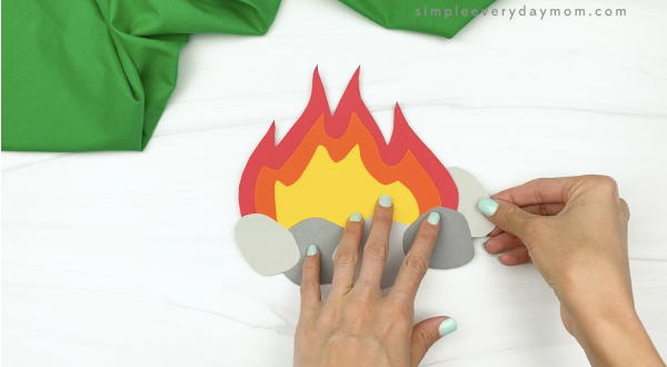 hand gluing rock to paper campfire craft