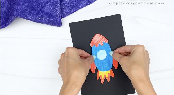hand gluing rocket onto black paper