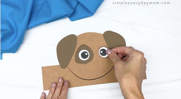 hand gluing eye to dog headband craft