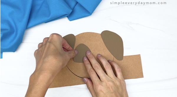 hand gluing eye spot to dog headband craft