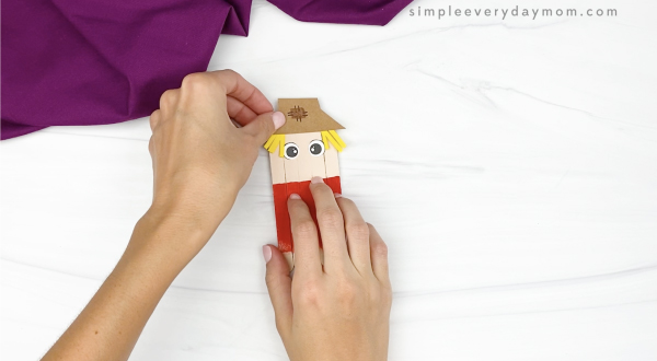 hand gluing hat onto popsicle stick scarecrow craft