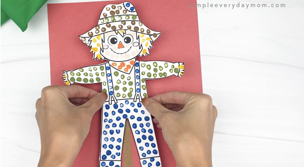 hand gluing paper scarecrow to red paper