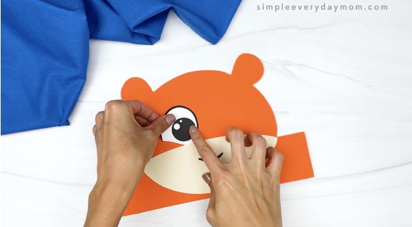 hand gluing eye to tiger headband craft