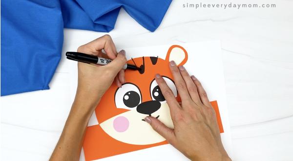 hand drawing stripes onto tiger headband craft