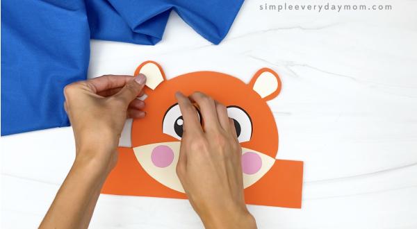 hand gluing inner ear to tiger headband craft