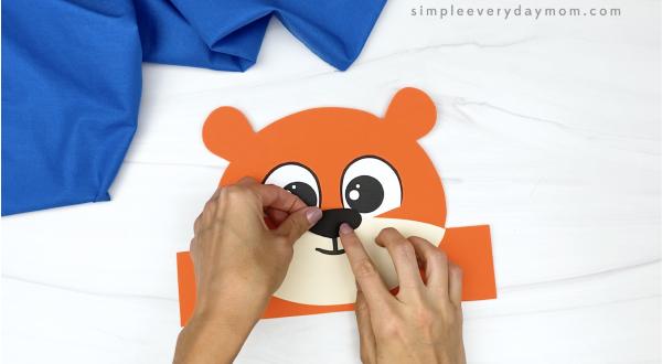 hand gluing nose to tiger headband craft