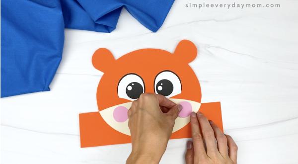 hand gluing cheek to tiger headband craft