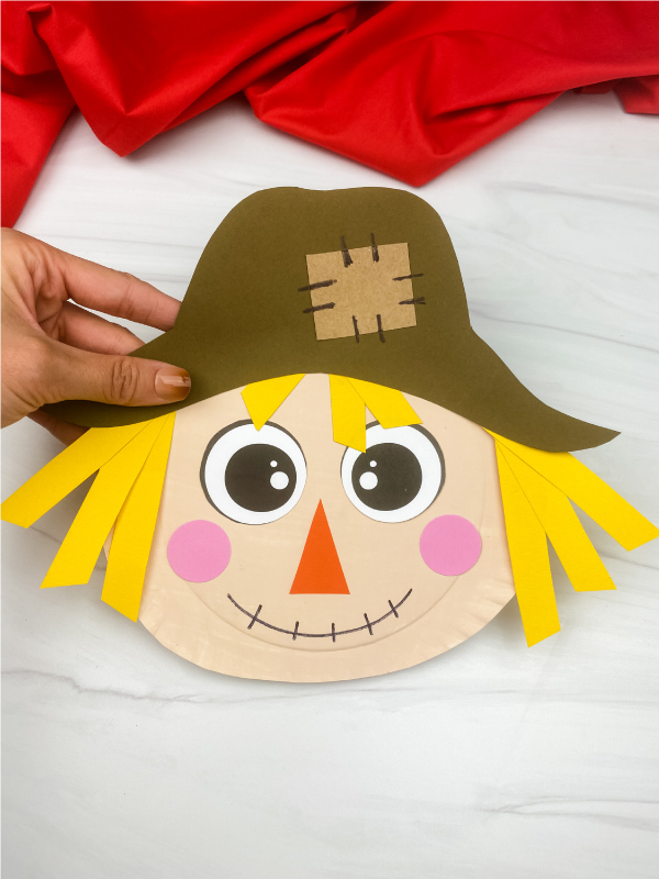 hand holding paper plate scarecrow craft