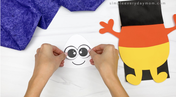hand gluing eyes to candy corn puppet craft