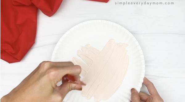 hand painting white paper plate cream