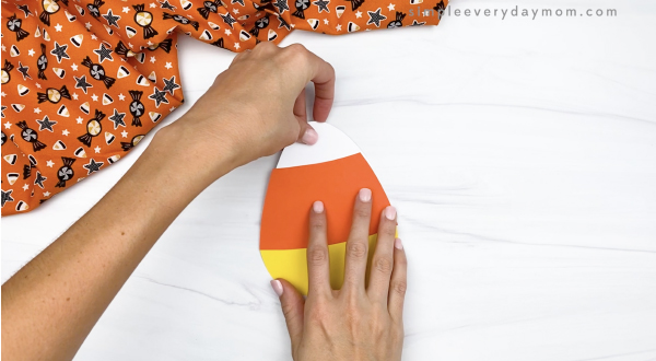 hand gluing candy corn top on