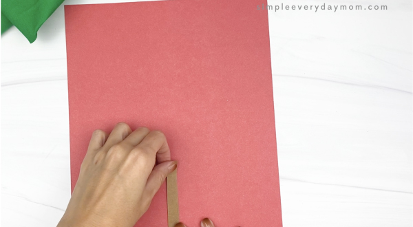 hand gluing brown rectangle to red paper