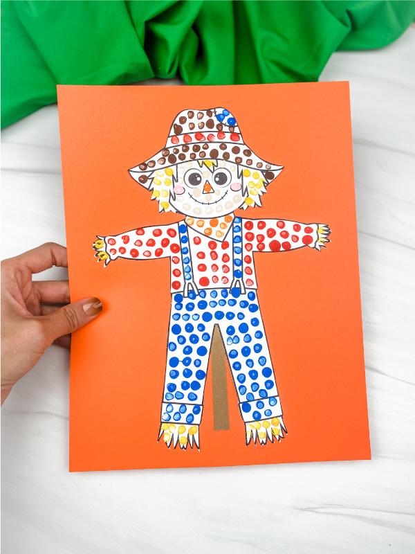 hand holding scarecrow dot art