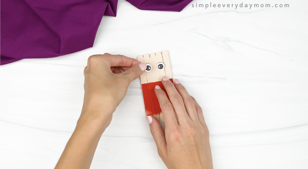 hand gluing eye onto popsicle stick scarecrow craft