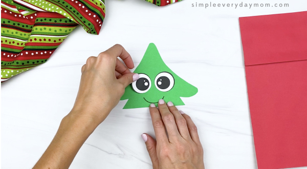hand gluing eyes to paper bag Christmas tree craft