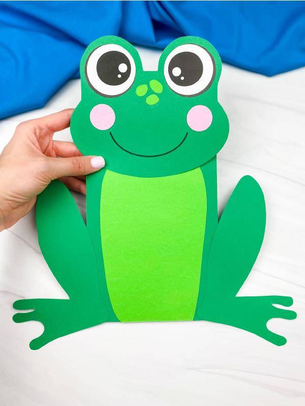 hand holding paper bag frog craft