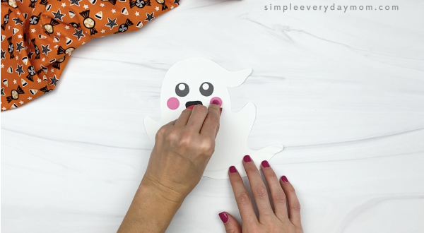 hand gluing cheek to paper plate ghost craft