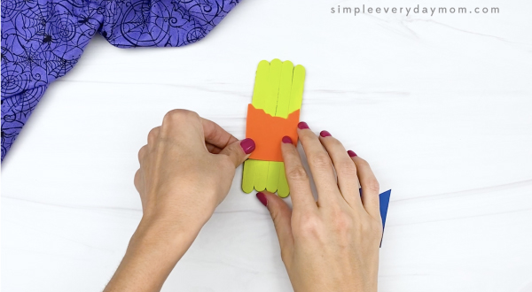 hand gluing shirt to popsicle stick zombie