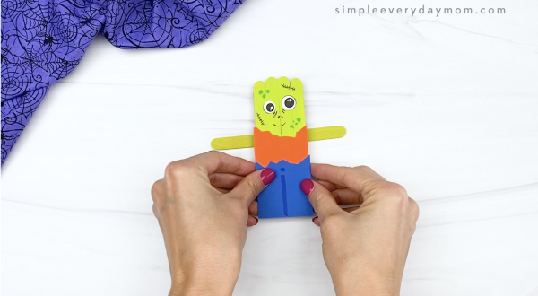 hand gluing arms to popsicle stick zombie