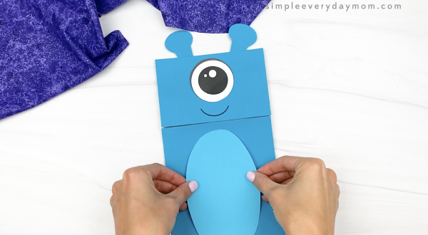 hand gluing belly to alien paper bag puppet craft